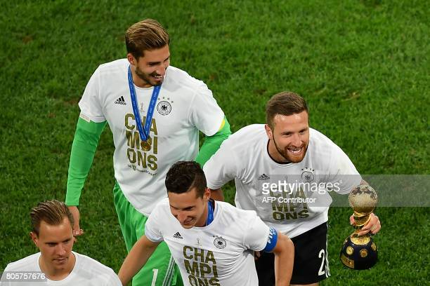 Germany's defender Shkodran Mustafi celebrates with the trophy after winning the 2017 Confederations Cup final football match between Chile and...