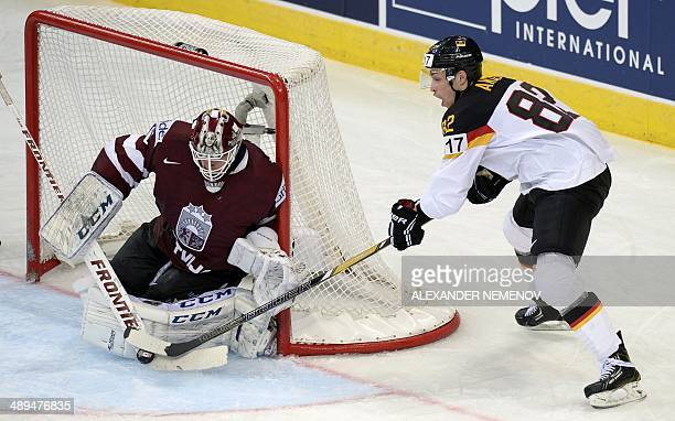 Germany's defender Sinan Akdag attacks Latvia's goalie Kristers Gudlevskis during a preliminary round group B game Germany vs Lavia of the IIHF...
