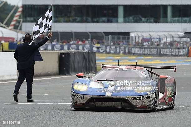 Germany's Dirk Mueller crosses the finish line on his Ford GT n°68 to win the LMGTE PRO category of the 84th Le Mans 24hours endurance race on June...