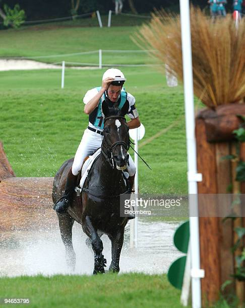 Germany's Dirk Schrade riding Grand Amour grabs hold of his silk as he emerges from the water jump during the cross country section of the Good Luck...