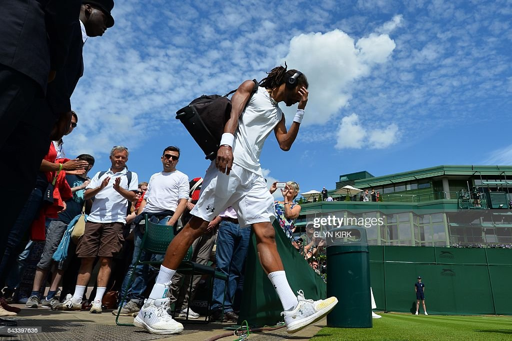 Germany's Dustin Brown arrives on court to play against Serbia's Dusan Lajovic during their men's singles first round match on the first day of the 2016 Wimbledon Championships at The All England Lawn Tennis Club in Wimbledon, southwest London, on June 28, 2016. / AFP / GLYN