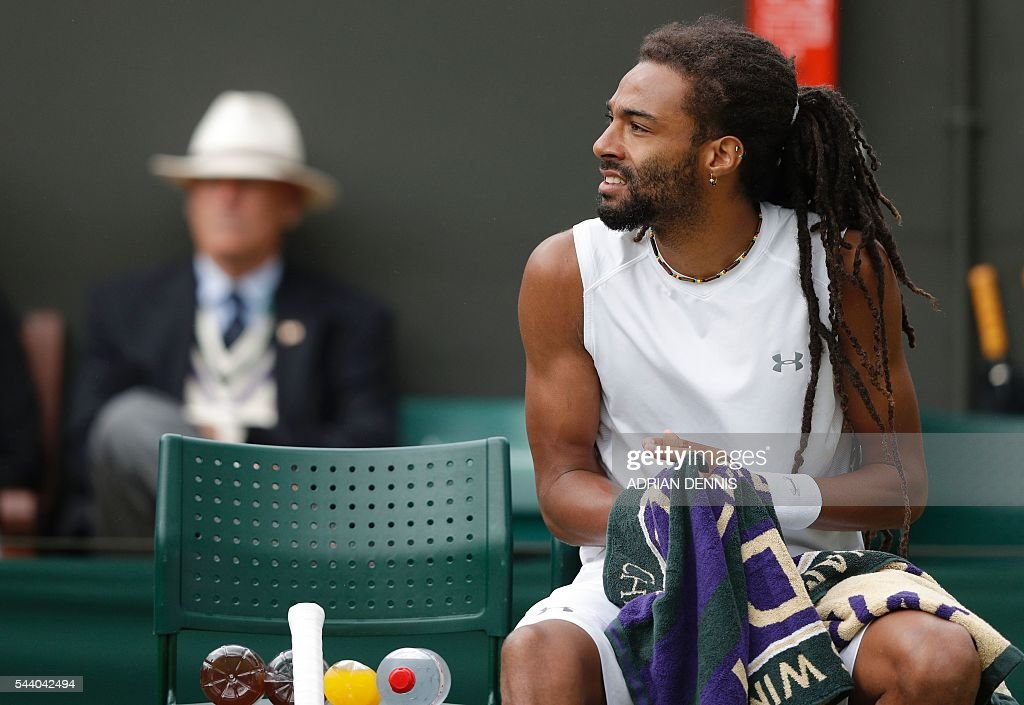 Germany's Dustin Brown dries his hands as rain stops play on the fifth day of the 2016 Wimbledon Championships at The All England Lawn Tennis Club in Wimbledon, southwest London, on July 1, 2016. / AFP / ADRIAN