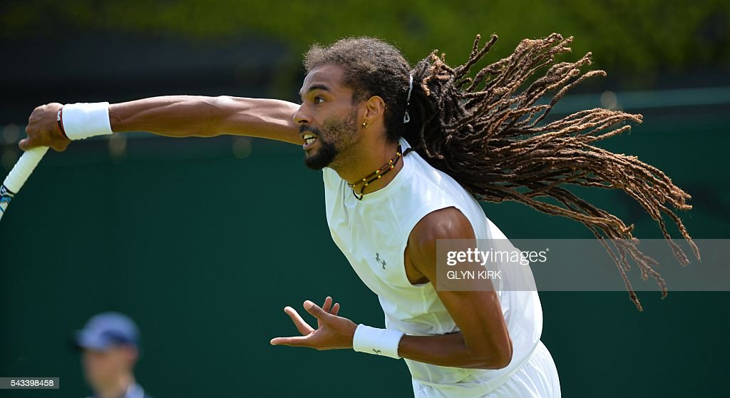 Germany's Dustin Brown serves against Serbia's Dusan Lajovic during their men's singles first round match on the second day of the 2016 Wimbledon Championships at The All England Lawn Tennis Club in Wimbledon, southwest London, on June 28, 2016. / AFP / GLYN