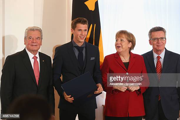 Germanys Federal President Joachim Gauck German Chancellor Angela Merkel and and German Minister of the Interior Thomas de Maiziere awards Erik Durm...