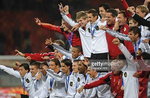 Germany's football squad sit on the podium as they celebrate their third place finish at the end of the 2010 World Cup third place football match...