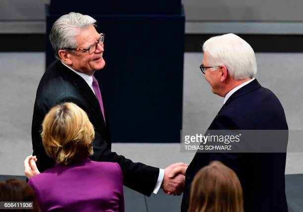 Germany's former President Joachim Gauck shakes hands with his successor FrankWalter Steinmeier during the swearingin ceremony for the new German...