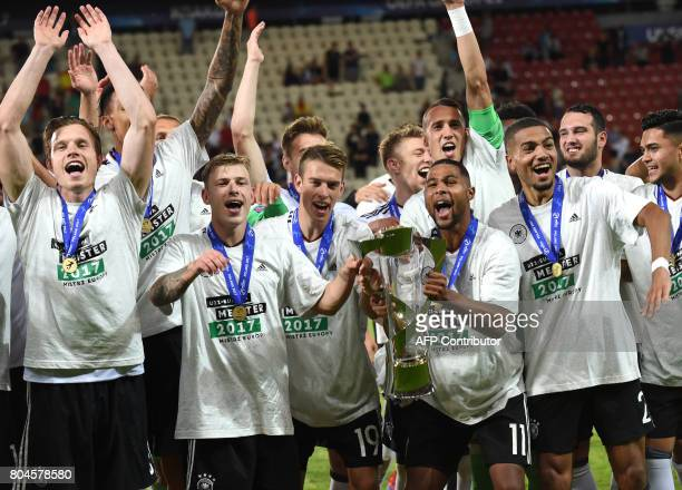 Germany's forward Janik Haberer Germany's midfielder Serge Gnabry Germany's defender Jeremy Toljan and teammates celebrate with the trophy after...