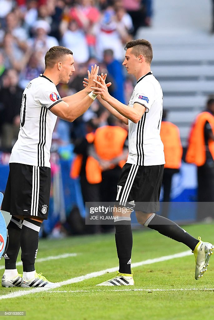 Germany's forward Lukas Podolski (L) replaces Germany's midfielder Julian Draxler during the Euro 2016 round of 16 football match between Germany and Slovakia at the Pierre-Mauroy stadium in Villeneuve-d'Ascq near Lille on June 26, 2016. / AFP / Joe KLAMAR