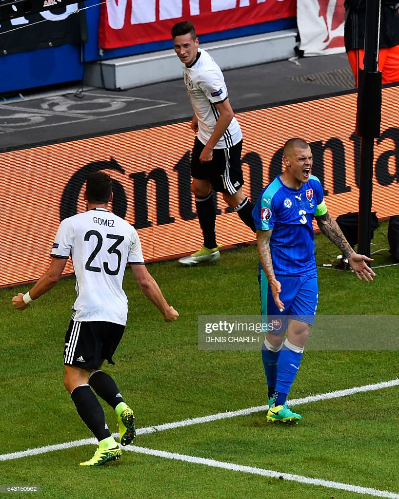 Germany's forward Mario Gomez (L) celebrates next to Germany's midfielder Julian Draxler and Slovakia's defender Martin Skrtel after scoring during the Euro 2016 round of 16 football match between Germany and Slovakia at the Pierre-Mauroy stadium in Villeneuve-d'Ascq, near Lille, on June 26, 2016. / AFP / DENIS