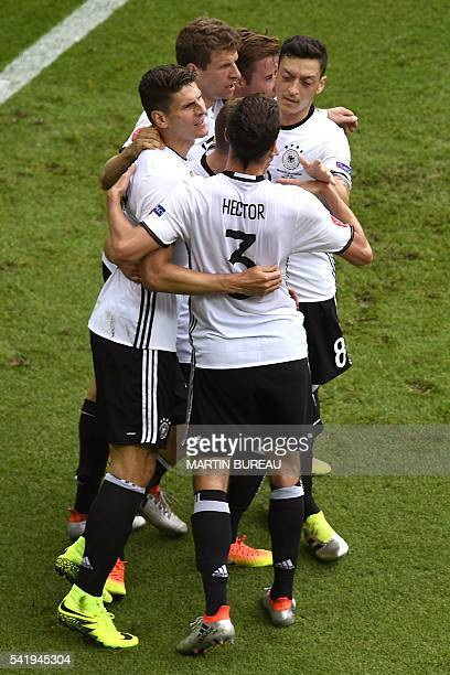 Germany's forward Mario Gomez celebrates with teammates after scoring his team's first goal during the Euro 2016 group C football match between...