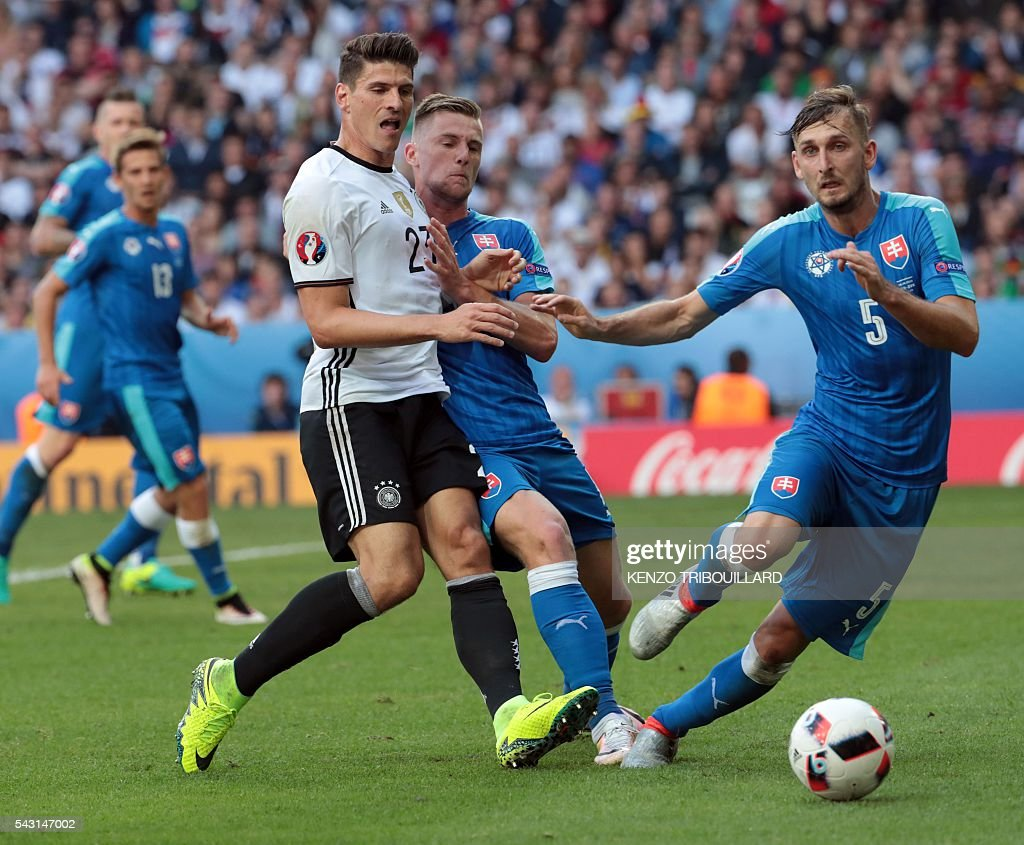 Germany's forward Mario Gomez (L) challenges Slovakia's defender Milan Skriniar (C) and Slovakia's defender Jan Durica during the Euro 2016 round of 16 football match between Germany and Slovakia at the Pierre-Mauroy stadium in Villeneuve-d'Ascq near Lille on June 26, 2016. / AFP / KENZO