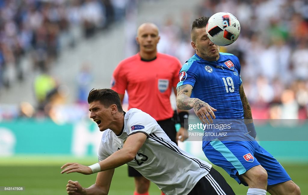 Germany's forward Mario Gomez (L) challenges Slovakia's midfielder Juraj Kucka during the Euro 2016 round of 16 football match between Germany and Slovakia at the Pierre-Mauroy stadium in Villeneuve-d'Ascq near Lille on June 26, 2016. / AFP / PATRIK