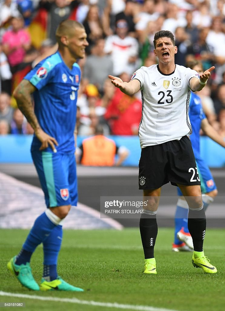 Germany's forward Mario Gomez (R) reacts next to Slovakia's defender Martin Skrtel during the Euro 2016 round of 16 football match between Germany and Slovakia at the Pierre-Mauroy stadium in Villeneuve-d'Ascq near Lille on June 26, 2016. / AFP / PATRIK