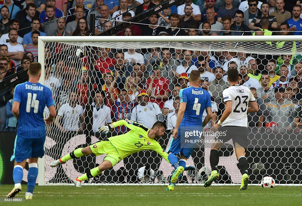 Germany's forward Mario Gomez (R) scores against Slovakia's goalkeeper Matus Kozacik during the Euro 2016 round of 16 football match between Germany and Slovakia at the Pierre-Mauroy stadium in Villeneuve-d'Ascq, near Lille, on June 26, 2016. / AFP / PHILIPPE