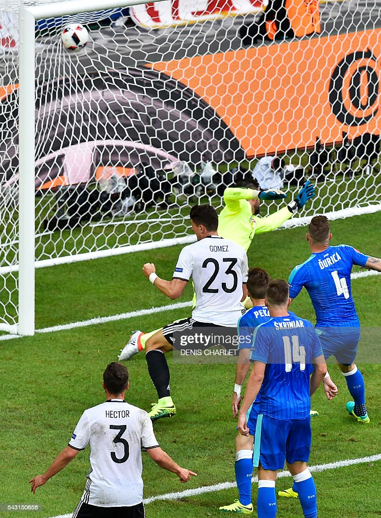 Germany's forward Mario Gomez (C) scores against Slovakia's goalkeeper Matus Kozacik during the Euro 2016 round of 16 football match between Germany and Slovakia at the Pierre-Mauroy stadium in Villeneuve-d'Ascq, near Lille, on June 26, 2016. / AFP / DENIS