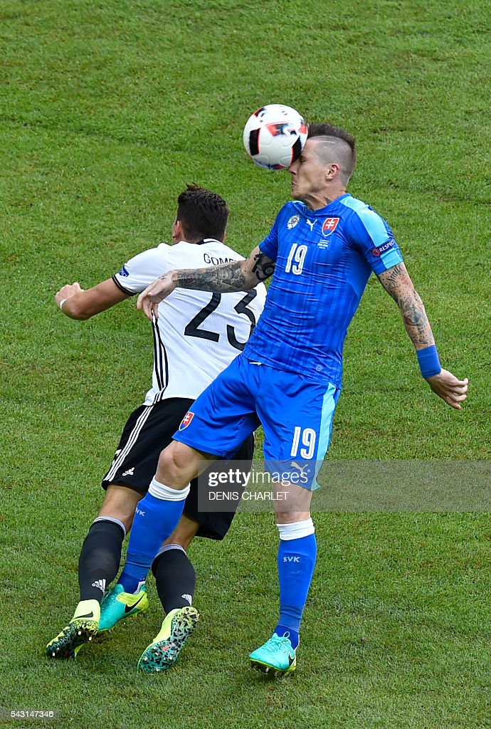 Germany's forward Mario Gomez (L) vies with Slovakia's midfielder Juraj Kucka during the Euro 2016 round of 16 football match between Germany and Slovakia at the Pierre-Mauroy stadium in Villeneuve-d'Ascq, near Lille, on June 26, 2016. / AFP / DENIS