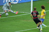 Germany's forward Thomas Mueller scores their first goal during the semifinal football match between Brazil and Germany at The Mineirao Stadium in...