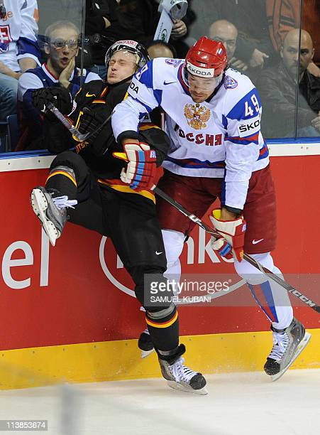 Germany's Frank Hordler and Russia's Yevgeni Artyukhin vie during the IIHF Ice Hockey World Championship gorup A match Germany vs Russia in...