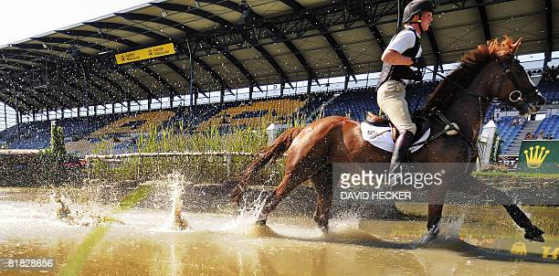 Germany's Frank Ostholt and his horse 'Mr Medicott' ride through the water after a jump during the CHIO World Equestrian Festival in Aachen western...