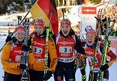 Germany's Franziska Hildebrand Franziska Preuss Luise Kummer and Laura Dahlmeier pose in the finish area after winning the Women's 4x6 km relay race...