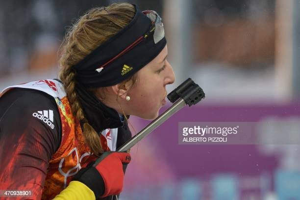 Germany's Franziska Preuss checks the sight of her rifle as she competes at the shooting range in the Women's Biathlon 4x6 km Relay at the Laura...