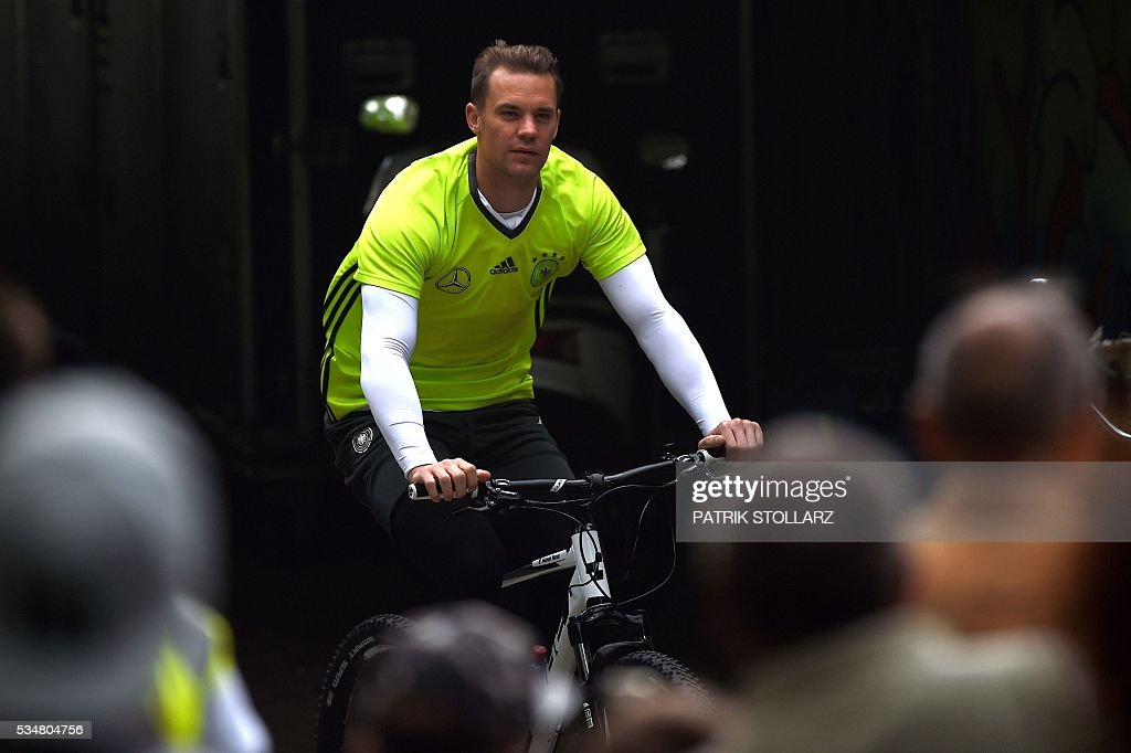 Germany's goalkeeper Manuel Neuer arrives with his bike at a training session as part of the team's preparation for the upcoming Euro 2016 European football championships, on May 28, 2016 in Ascona. / AFP / PATRIK