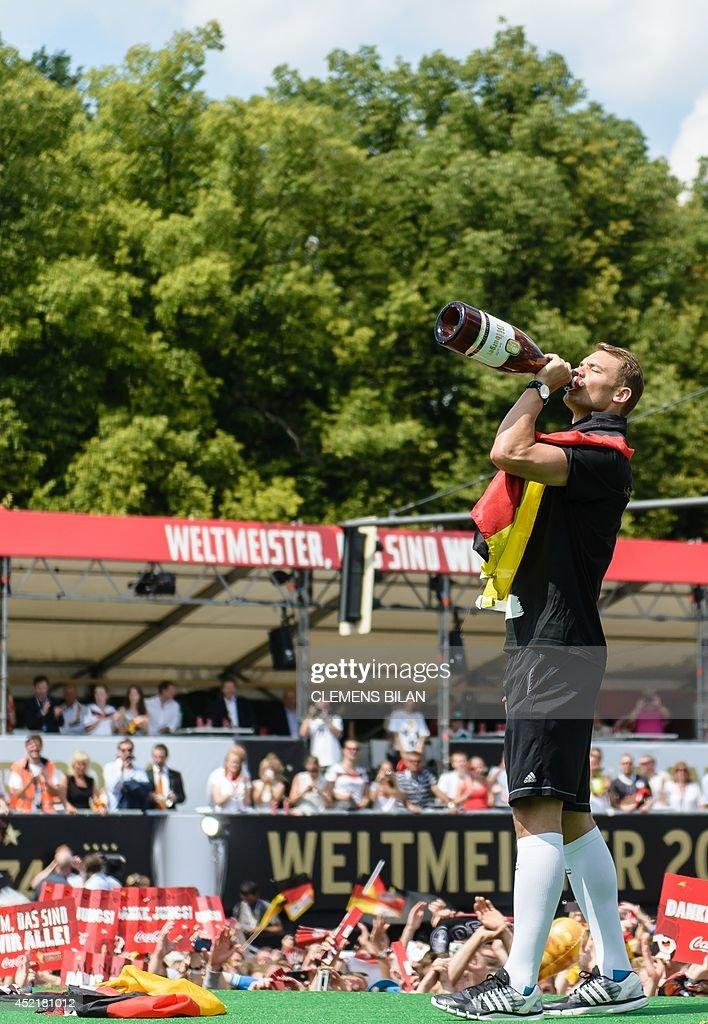 Germany's goalkeeper Manuel Neuer drinks from a giant beer bottle on a stage at the 'Fanmeile' area, where fans welcomed players and members of Germany's football national team on July 15, 2014 at Berlin's landmark Brandenburg Gate to celebrate their FIFA World Cup title. Germany won their fourth World Cup title, after their 1-0 win over Argentina on July 13, 2014 in Rio de Janeiro in the FIFA World Cup Brazil final game. AFP PHOTO / CLEMENS BILAN