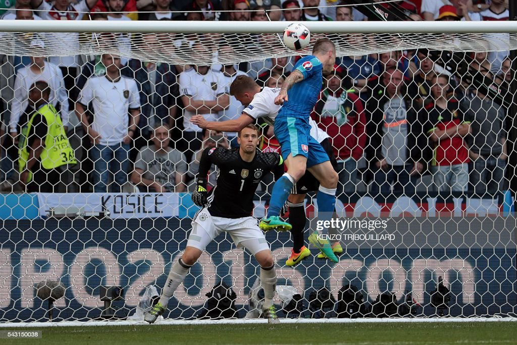 Germany's goalkeeper Manuel Neuer (back) eyes the ball as Germany's midfielder Joshua Kimmich challenges Slovakia's midfielder Juraj Kucka (front) during the Euro 2016 round of 16 football match between Germany and Slovakia at the Pierre-Mauroy stadium in Villeneuve-d'Ascq near Lille on June 26, 2016. / AFP / KENZO