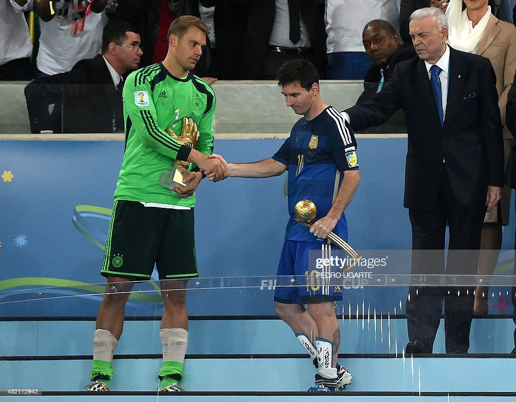 Germany's goalkeeper Manuel Neuer holds his Goldan Glove trophy awarded to the best goalkeeper of the tournament and Argentina's forward and captain...