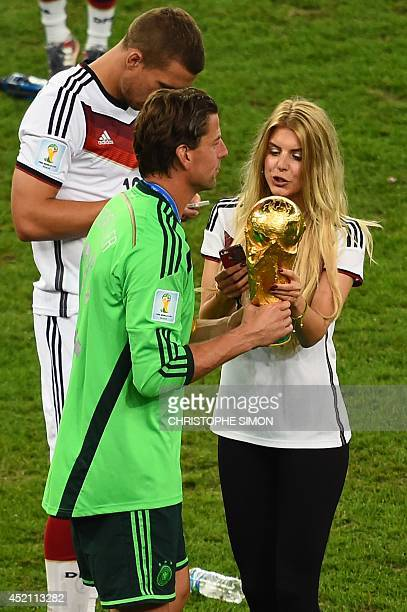 Germany's goalkeeper Roman Weidenfeller and his girlfriend Lisa Rossenbach hold the World Cup trophy after the final football match between Germany...