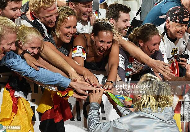 Germany's gold medallist Laura Ludwig celebrates with supporters at the end of the women's beach volleyball event at the Beach Volley Arena in Rio de...