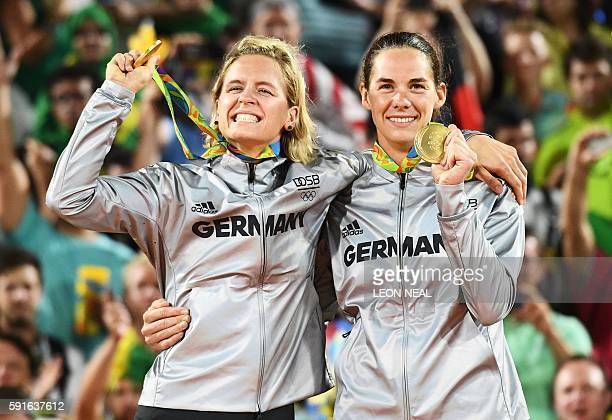 Germany's gold medallists Laura Ludwig and Kira Walkenhorst celebrate on the podium at the end of the women's beach volleyball event at the Beach...