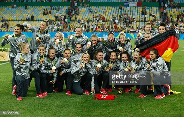 Germany's gold medallists pose for photographers following the women's football medal ceremony of the Rio 2016 Olympic Games at the Maracana stadium...