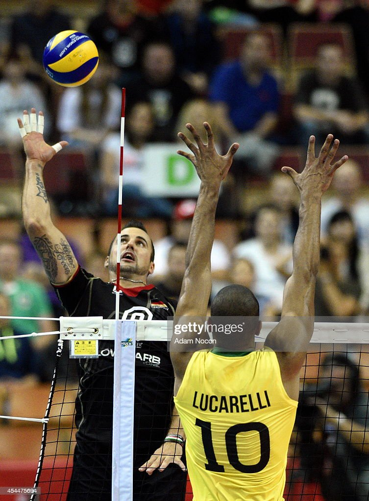 Germany's Grozer Gyorgy attacks Brazil's defense Lucarelli Ricardo during the FIVB World Championships match between Brazil and Germany on September 1, 2014 in Katowice, Poland.