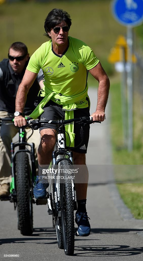 Germany's head coach Joachim Loew arrives by bike to a training session as part of the team's preparation for the upcoming Euro 2016 European football championships, on May 26, 2016 in Ascona. / AFP / PATRIK