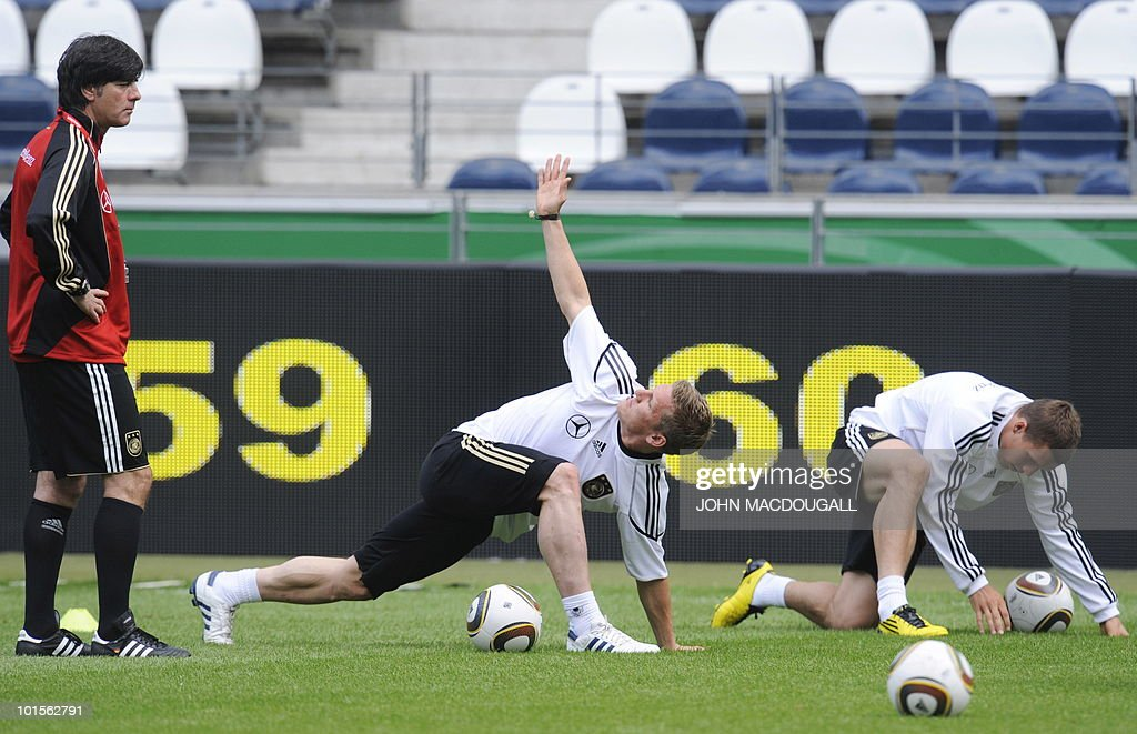 Germany's head coach Joachim Loew (L) looks on as German midfielder Bastian Schweinsteiger (C) and German forward Lukas Podolski perform warm up exercises during a training session at the Commerzbank Arena in the central German city of Frankfurt am Main on June 2, 2010. Germany is facing Bosnia-Herzegovina on June 3, 2010 in their last warm-up ahead of the FIFA 2010 World Cup in South Africa.