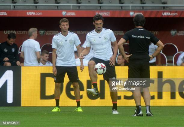 Germany's Head coach Joachim Loew oversees a training session of his players including Germany's midfielder Thomas Mueller and Germany's defender...