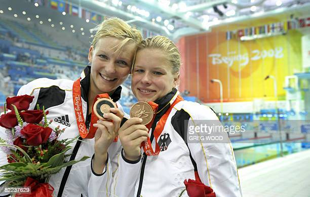 Germany's Heike Fischer and Ditte Kotzian pose with their bronze medals after the women's synchronised 3m springboard diving competition final at the...