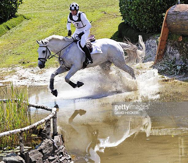 Germany's Hinrich Romeike and his horse 'Marius VoigtLogistik' ride through the water after a jump during the CHIO World Equestrian Festival in...