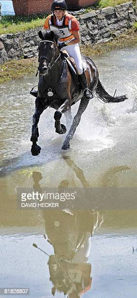 Germany's Ingrid Klimke and her horse 'FRH Butts Abraxxas' rides through the water after a jump during the CHIO World Equestrian Festival in Aachen...