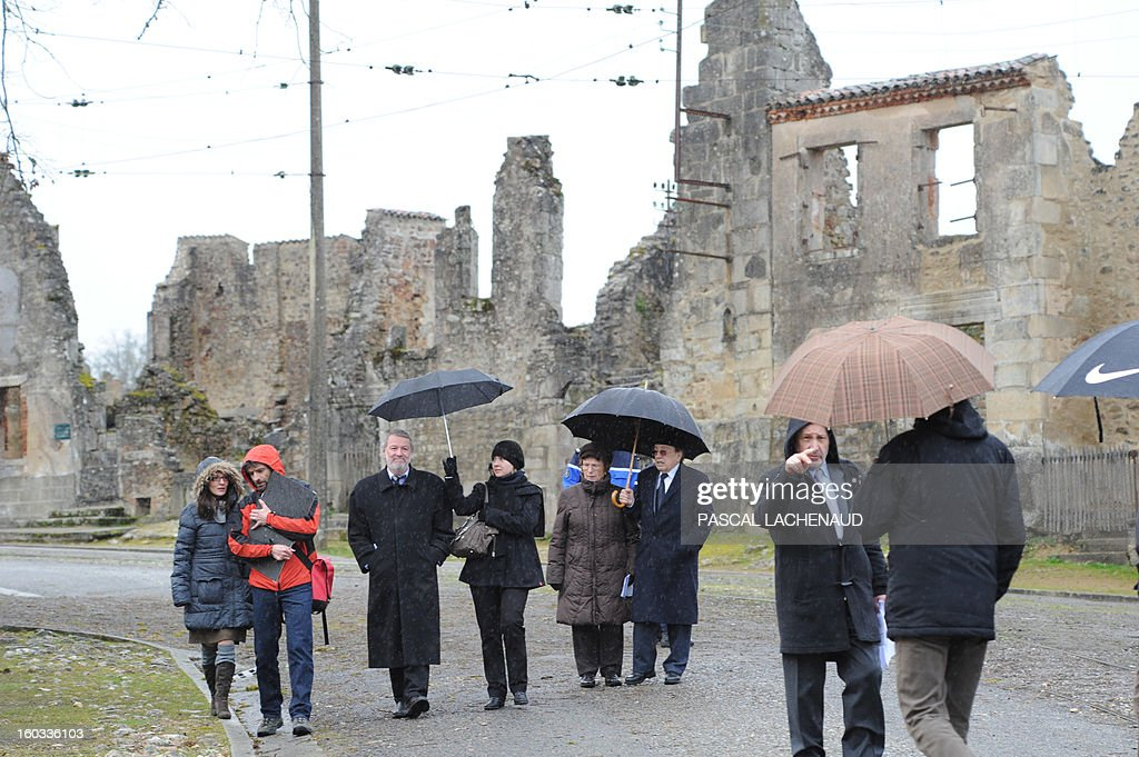 Germany's investigators (L), flanked by Dortmund Prosecutor substitute (3rd-L), French mayor of Oradour-sur-Glane, Raymond Frugier (3rd-R) and French historian, Pascal Plas (2nd-R), walk in the main street of the village of Oradour-sur-Glane, southern France, on January 29, 2013. An investigation for crimes of war is led by German and French authorities 68 years after the 1944 massacre. On June 10, 1944, a detachment of the SS Das Reich division were ordered to destroy the village and all of its inhabitants, killing 642 persons. AFP PHOTO PASCAL LACHENAUD