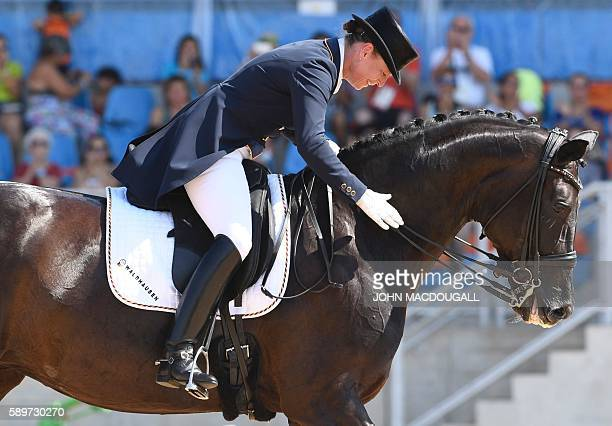 Germany's Isabell Werth pats her horse Weihegold Old after performing her routine to win the silver medal in the Equestrian's Dressage Grand Prix...
