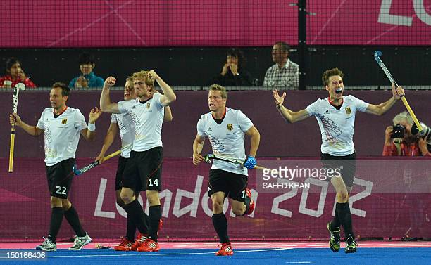 Germany's Jan Philipp Rabente celebrates a goal with Matthias Witthaus Jan Philipp Rabente and other teammates during the men's field hockey gold...