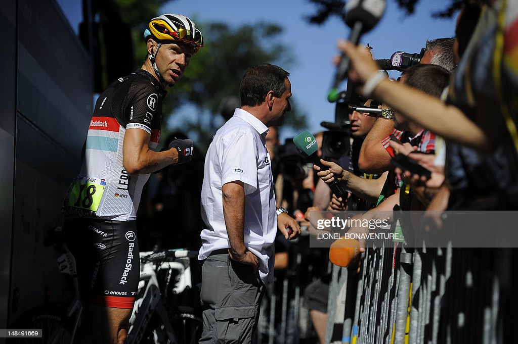 Germany's Jens Voigt (L) stands next to Philippe Maertens, Luxembourger Radioshack cycling team's spokesman, answering journalists' questions prior to the beginning of the 197 km and sixteenth stage of the 2012 Tour de France cycling race starting in Pau and finishing in Bagneres de Luchon, southern France, on July 18, 2012. Luxembourg's Frank Schleck (Radioschack), a former podium finisher at the Tour de France, has tested positive for a banned diuretic on July 14, 2012, the International Cycling Union (UCI) announced yesterday. AFP PHOTO / LIONEL BONAVENTURE