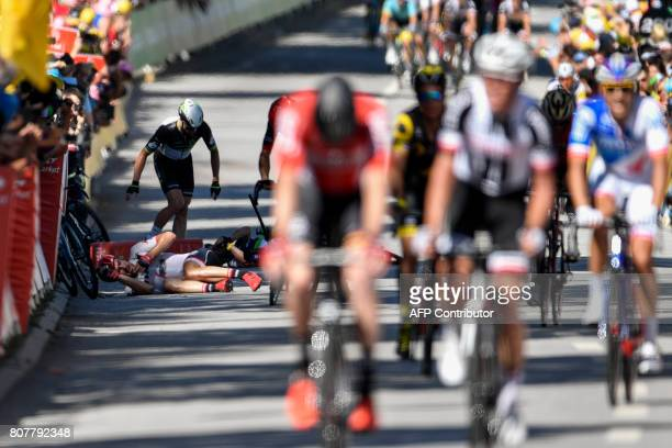 Germany's John Degenkolb and Great Britain's Mark Cavendish lie on the ground after falling near the finish line at the end of the 2075 km fourth...