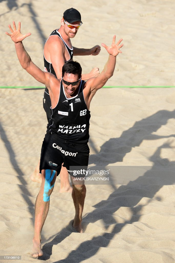 Germany's Jonathan Erdmann (front) and Kay Matysik react after they defeated Brazil's Alison Cerutti and Emanuel Rego (both not pictured) during the third place match of the Beach Volleyball World Championships on July 7, 2013 in Stare Jablonki, Poland.