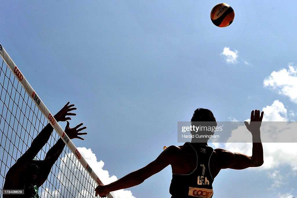 Germany's Jonathan Erdmann (R) attacks as Brazil's Pedro Salgado (L) defends during the Erdmann-Matysik v Pedro-Bruno match as part of the FIVB Gstaad Grand Slam fifth day on July 13, 2013 in Gstaad, Switzerland.
