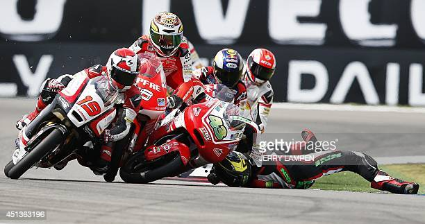 Germany's Luca Grunwald of the Kiefer Racing team falls with Spain's Juanfran Guevara of the Mapfre Aspar Team in the Moto3 race at the Dutch TT...