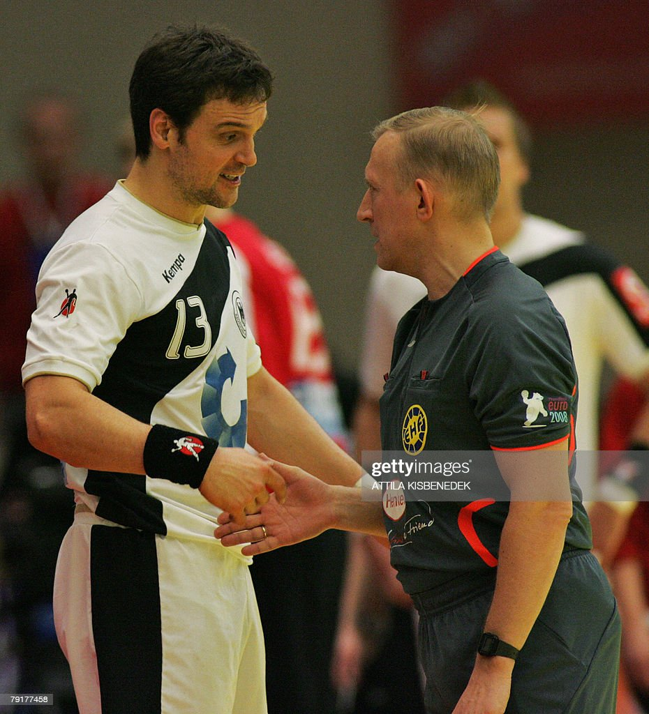 Germany's middle back Markus Baur (L) argues with Russian referee Victor POladenko during a time-out in their 8th Men's European Handball Championship Main Round match, 23 January 2008 at the Spektrum sports hall in Trondheim.