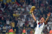 Germany's midfielder Bastian Schweinsteiger celebrates holding the World Cup trophy after the final football match between Germany and Argentina for...